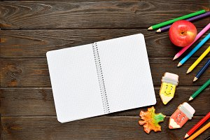 Back to school concept. Open notebook and apple with colored pencils, gingerbread on wooden background