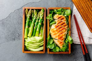 Healthy lunch in wooden japanese bento box. Balanced healthy food grilled chucken and avocado with asparagus and green salad. Top view, slate gray background