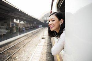 Cheerful Asian woman riding a train