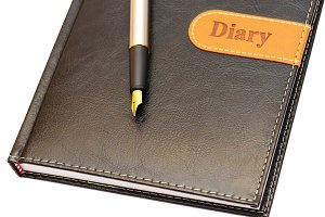 gold pen lying on a diary