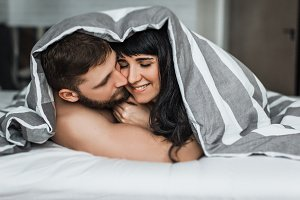 Loving couple lying under blanket