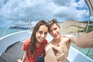 happy young smiling woman with boyfriend or husband make selfie in the white boat