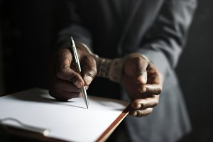 Man signing paper with handcuffs