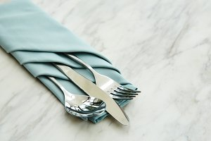 spoon and fork tied on a blue napkin on marble