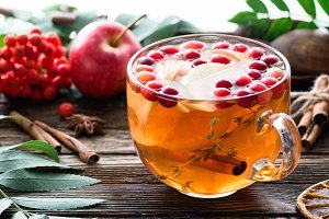 Hot apple cranberry cinnamon tea in glass cup on wooden table