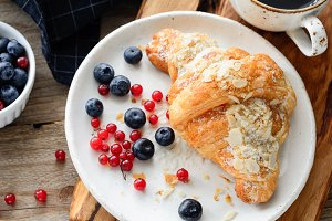 Fresh croissant with berries and cup of coffee