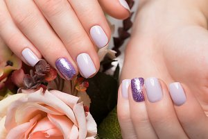 Purple neat manicure on female hands on flowers background. Nail design