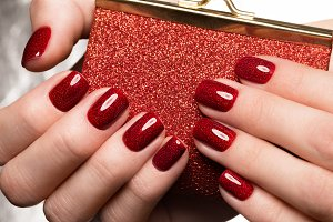 Bright festive red manicure on female hands. Nails design