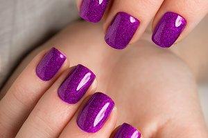 Bright festive purple manicure on female hands. Nails design
