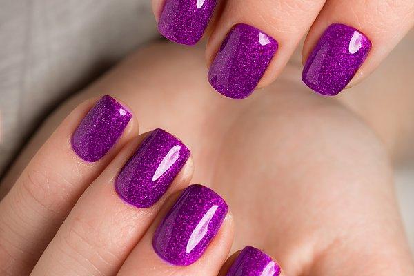 Bright festive purple manicure on f…