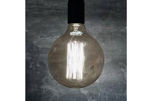 Close-up of a large burning retro light bulb. Concept of ideas and creativity.