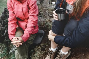 Two unrecognizable girls traveler in warm clothes sit on a rock and drink tea or coffee while relaxing