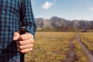 Unrecognizable Man Holding Trekking Poles On Mountain Background