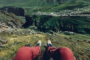 Traveler Man resting on a mountain plateau. POV view, legs close up on the