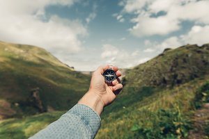 Male hand with compass on background of mountains in summer, point of view