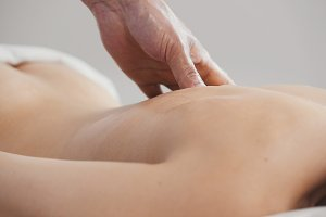 Spa. Massage for young woman - buttock and back, close up