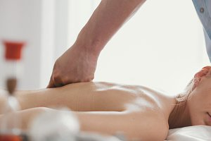 Blonde young woman receiving acupressure massage at spa