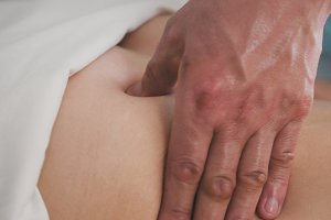 Massage - man's hand on woman's body - buttock, close up