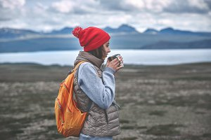 Cheerful woman drink tea on nature