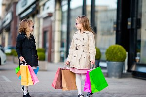 Kids on shopping bags walking in the city outdoors