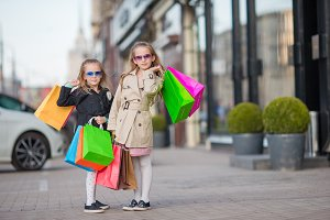 Adorable little girls on shopping in the city outdoors