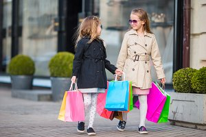 Adorable little girls with shopping bags walking in the city outdoors