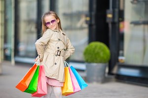 Adorable little girl walking with shopping bags outdoors in Europe. Fashion toddler kid in european city outdoors