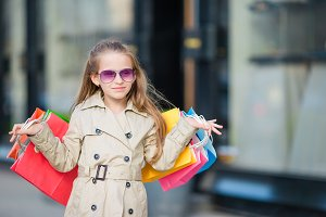 Portrait of adorable little girl with shopping bags outdoors. Fashion toddler kid in european city outdoors