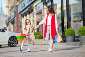Adorable little girl and happy mother walking with shopping bags in Europe outdoors