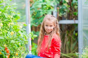 Adorable little girl in greenhouse in summer day