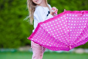Little adorable girl outdoors with umbrella