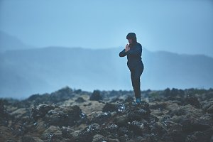 Woman hiker stands in yoga pose on volcanic Lava fields on background of mountains of Iceland.
