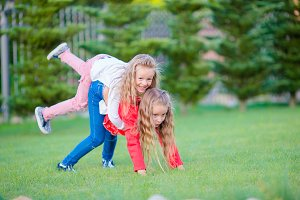 Little happy girls are having fun around on a green lawn