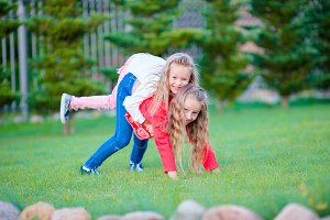 Little happy girls have a lot of fun outdoors in the park