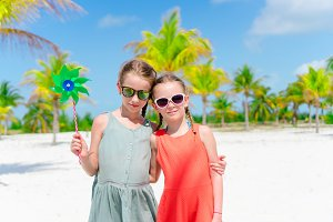 Adorable little girls during summer tropical vacation in palm grove