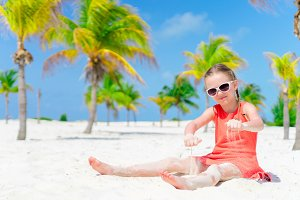 Little girl play on the beach during tropical vacation in palm grove