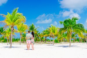 Young couple on white beach outdoors. Happy family enjoy their honeymoon in palm grove