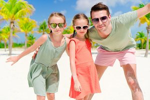 Father and little girls having fun on white beach in palm grove