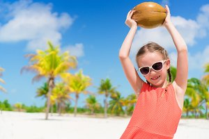 Little happy girl with big coconut on the beach in the palm grove