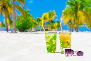 Two cold tasty mohito cocktails and white sunglasses on the white sandy beach