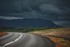 plot of asphalt road in a severe cloudy mountain landscape