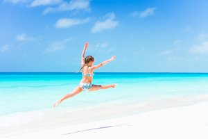 Active little girl at beach having a lot of fun on the shore making a leap