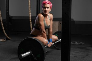 young woman sits at gym with barbells on floor