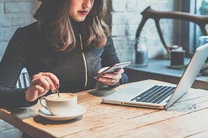 Young woman sitting in coffee shop at wooden table, drinking coffee and using smartphone.On table is laptop. Girl browsing internet, chatting, blogging. Female holding phone and looking on his screen.