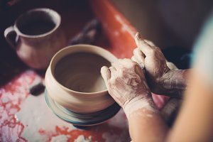 Work in a pottery workshop, womans hands creating ceramics.