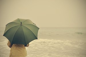 woman with green umbrella on the beach on a rainy day