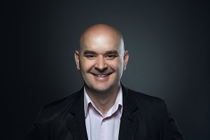 Portrait of a bald smiling, affable man in a suit against a dark background