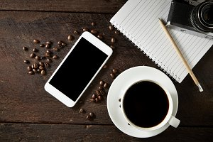 cup of coffee and smartphone on the wood texture