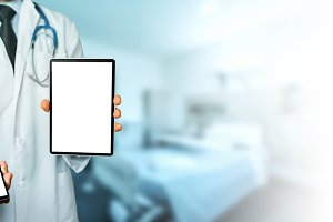 Unrecognizable male doctor in  white coat with  stethoscope hol smartphone and tablet, digital patient support system, test results and data registration
