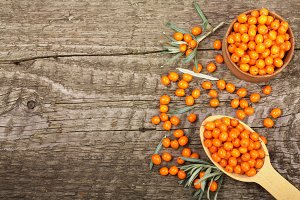 Sea buckthorn. Ripe fresh berries in bowl on old wooden background with copy space for your text. Top view